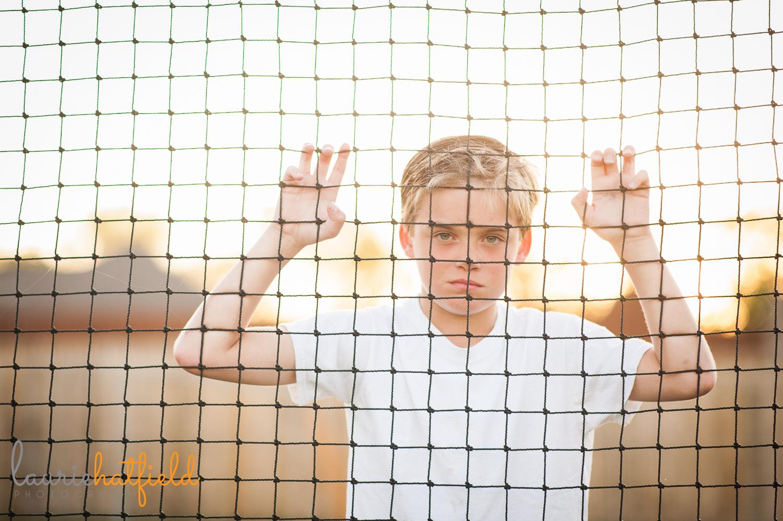 boy looking through soccer net | Huntsville photographer