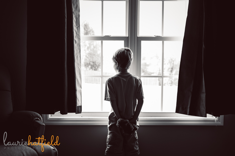 little boy standing at window holding stuffed animal | Huntsville child photographer