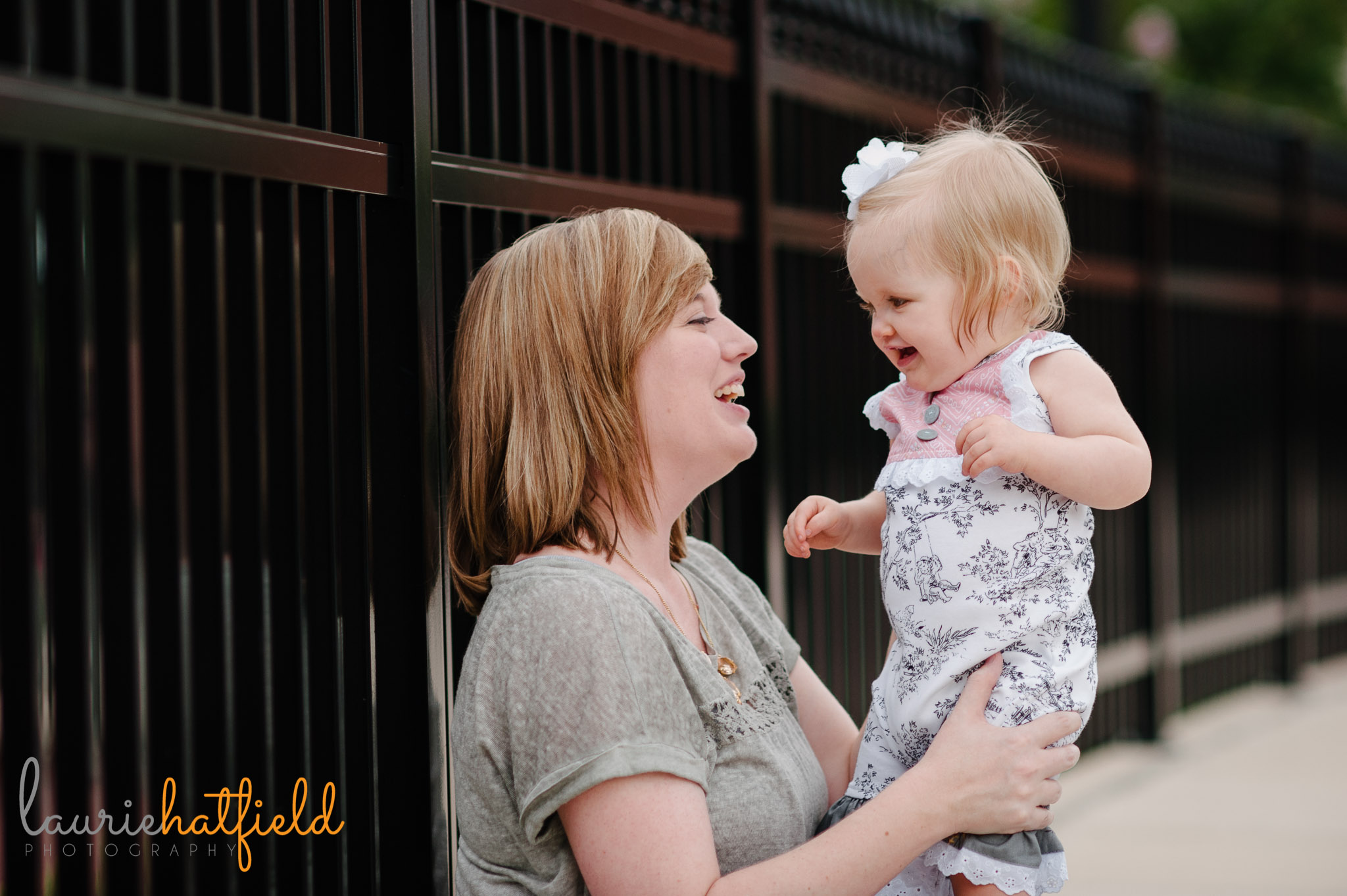 mom and one year old baby sitting against fence   Mobile AL photographer