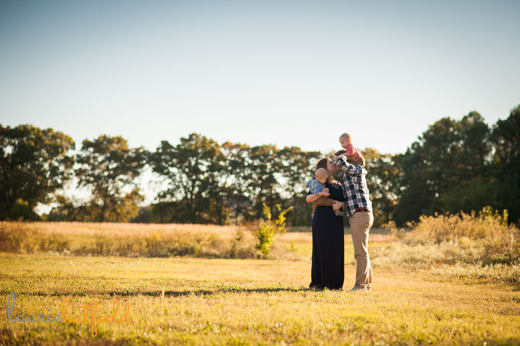 family of four walking in field   Mobile AL photographer
