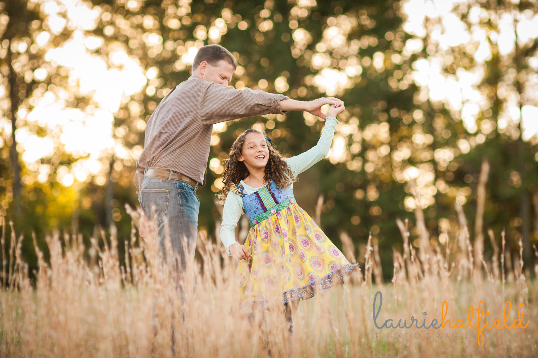 dad twirling daughter in tall grass | Mobile AL family photographer