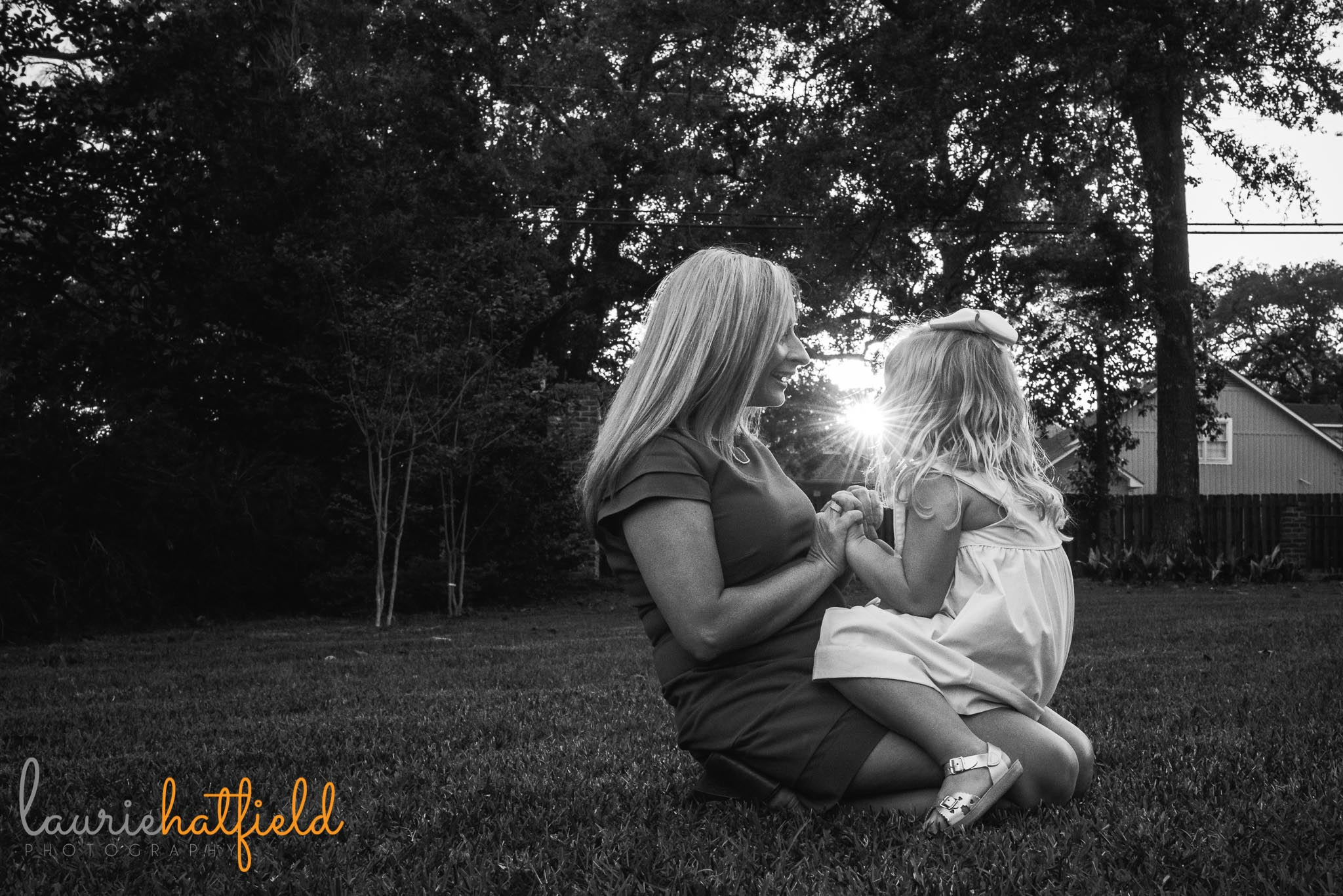 mom sitting with little girl on grass by Mobile AL family photographer Laurie Hatfield Photography