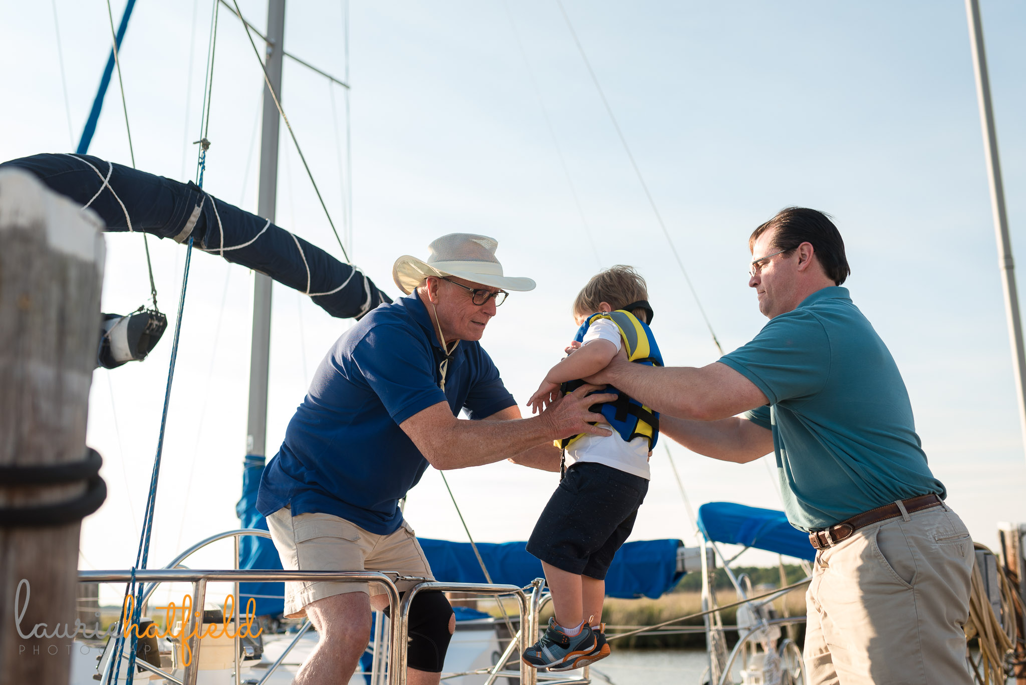 dad and grandfather helping boy onto boat | Mobile AL extended family photo session