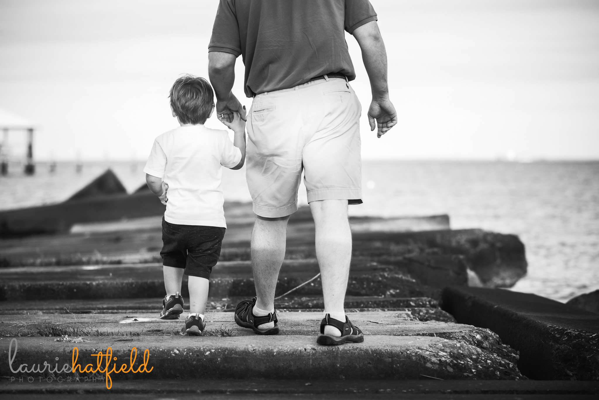 dad and 3-year-old son walking on rocks | Mobile AL family photographer