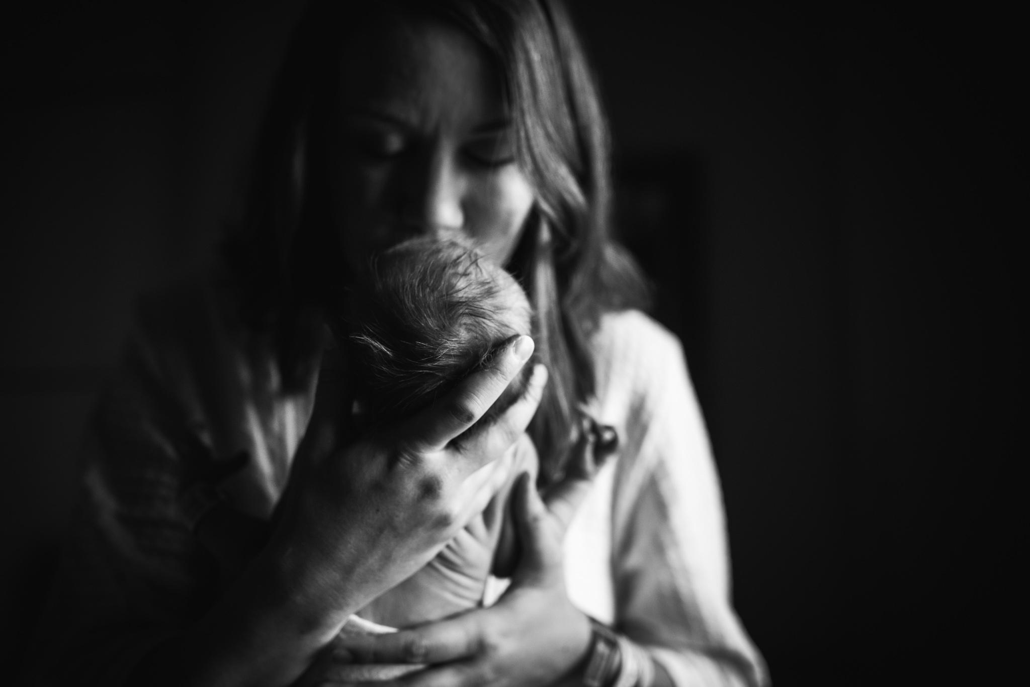 mom kissing newborn baby girl | Mobile AL in-hospital photo session