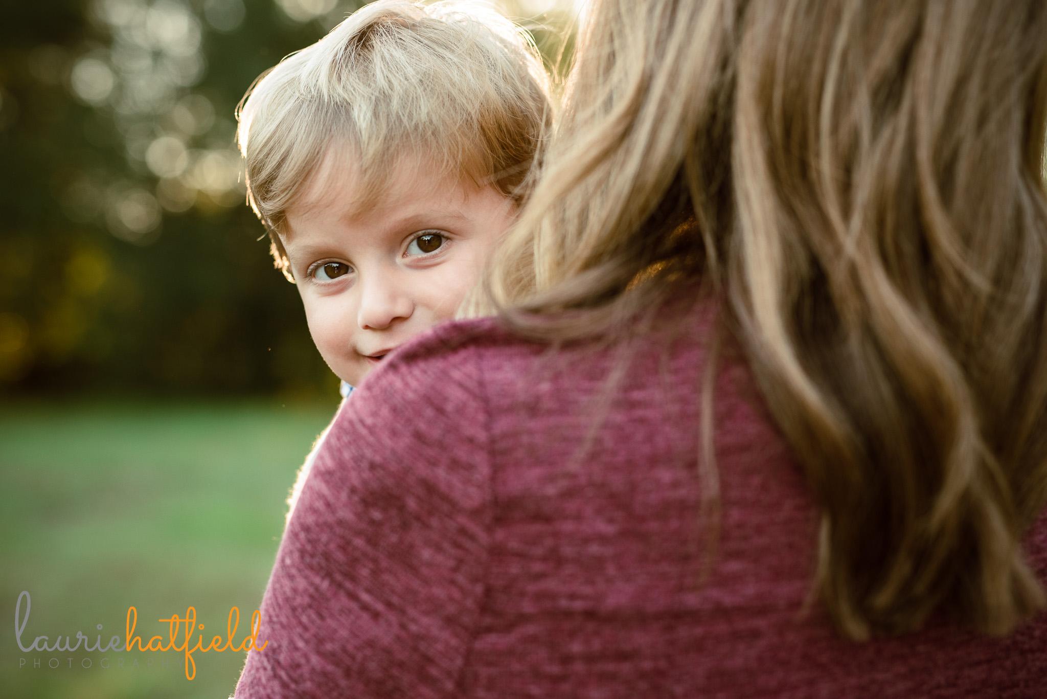 little boy peeking over mom's shoulder | Mobile AL family photographer