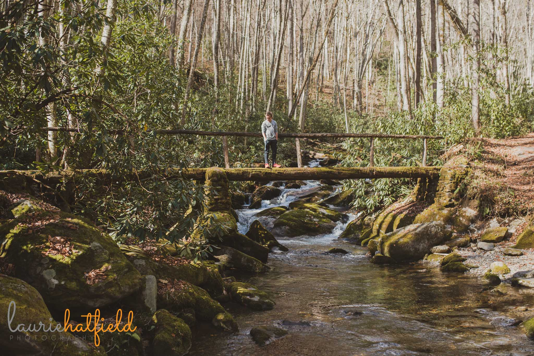 boy standing on bridge over creek | Mobile AL family photographer