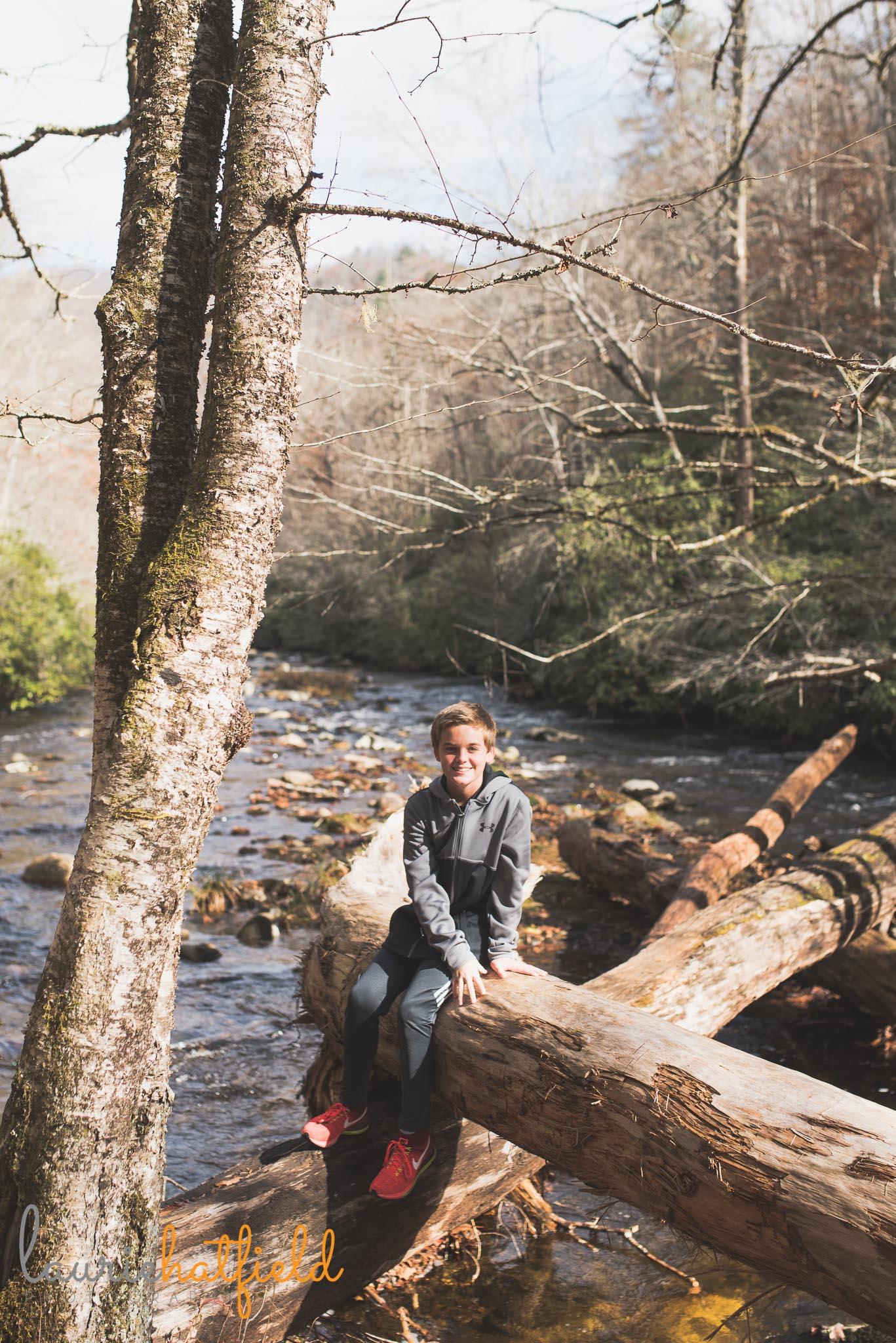 boy sitting on log over river | Mobile al family photographer