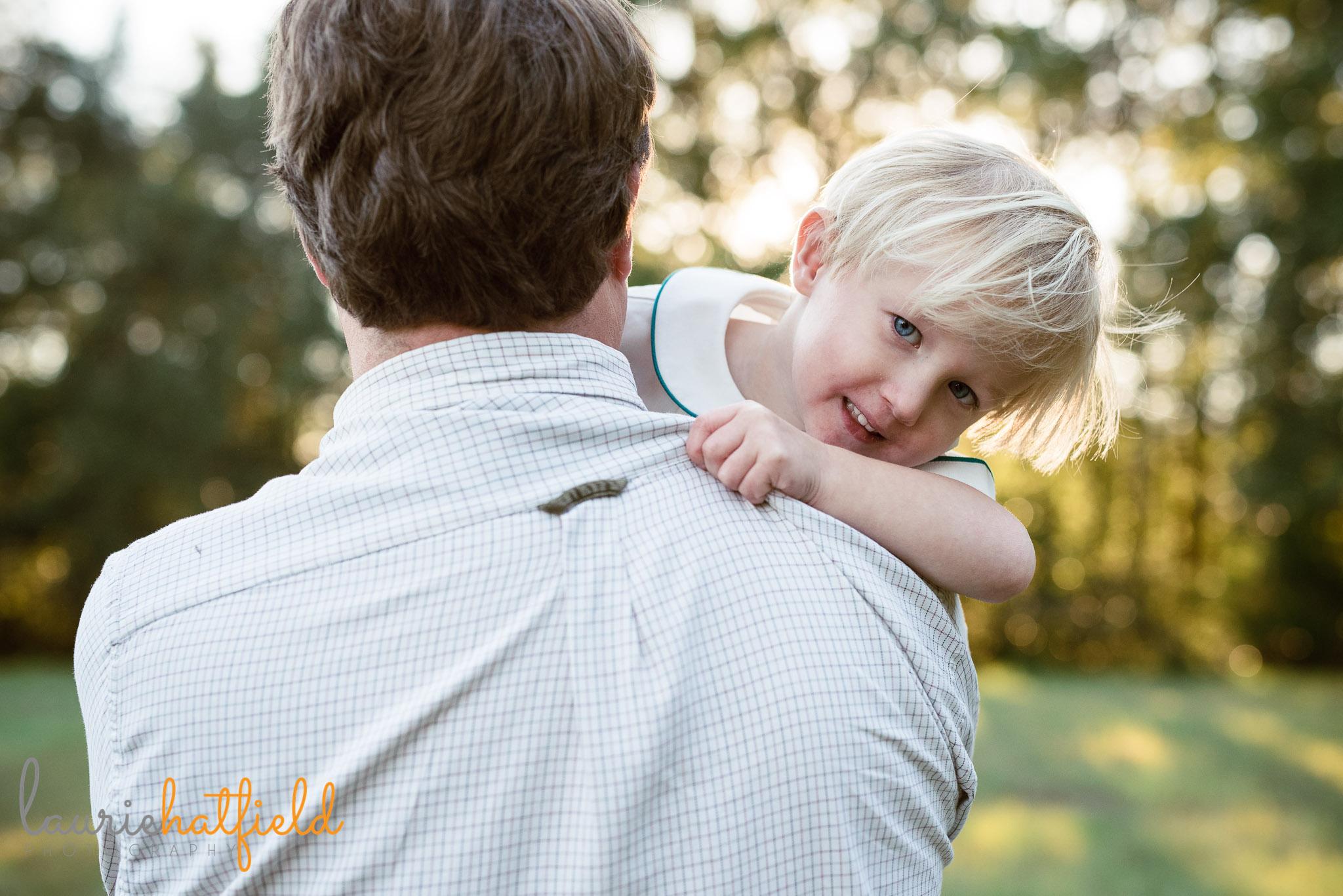 little boy peeking over dad's shoulder | Fairhope AL family photographer