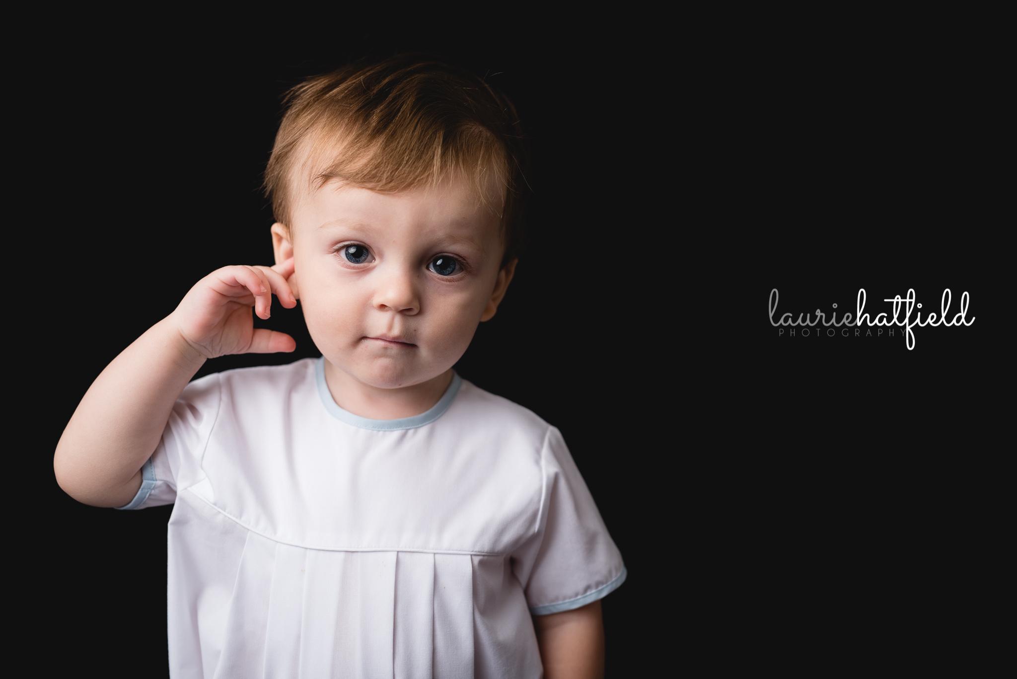 little boy with finger in ear   Mobile AL fine art school photography