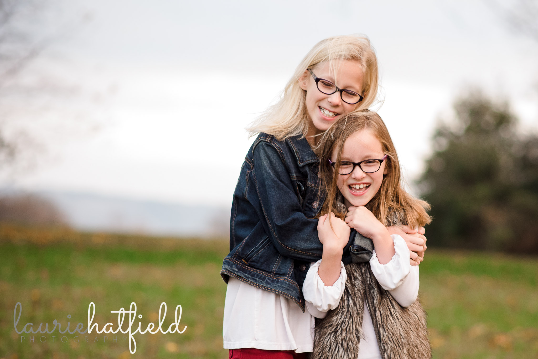 two sisters hugging in field | Mobile AL family photographer