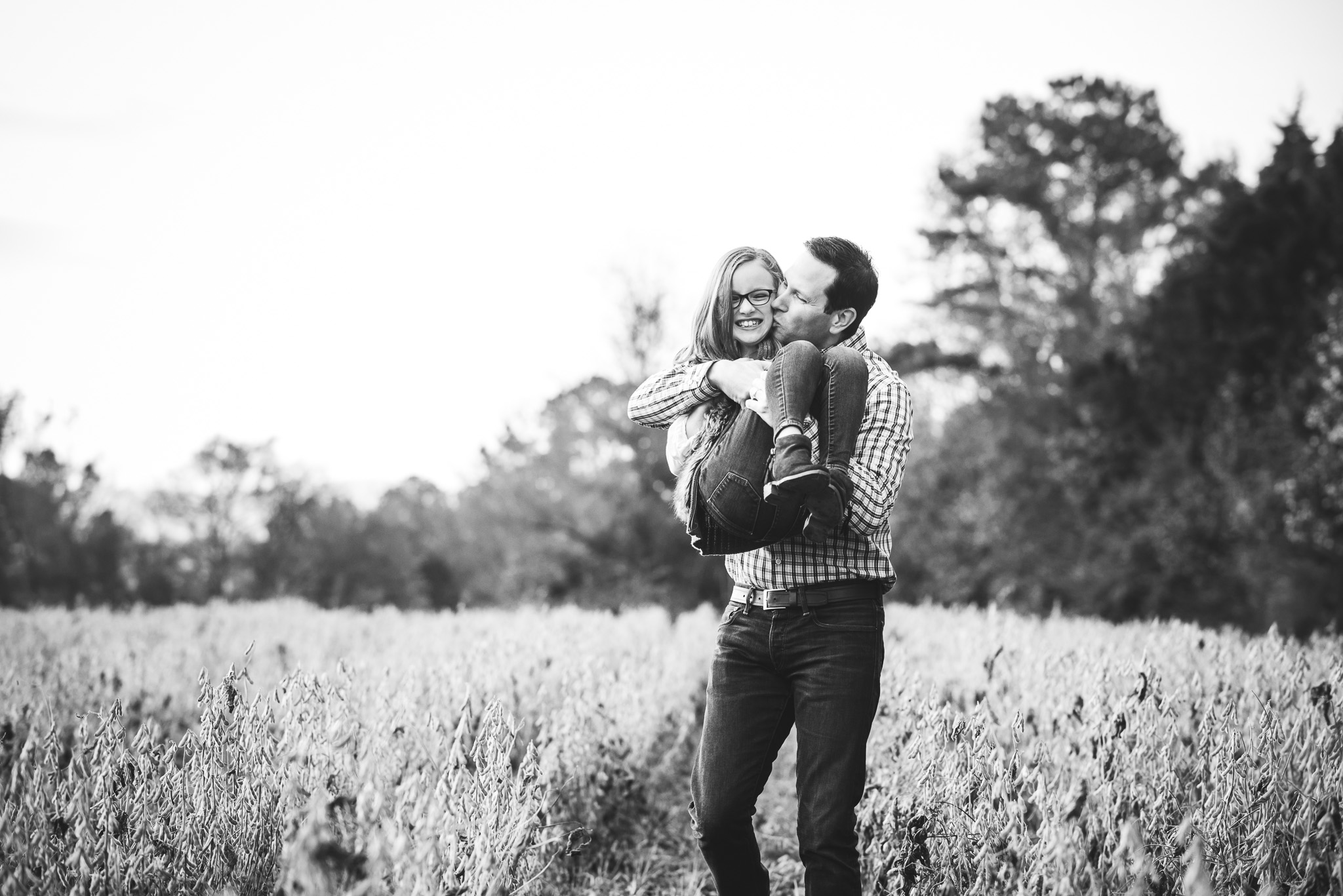 dad holding 8-year-old daughter in field | Mobile AL family photographer