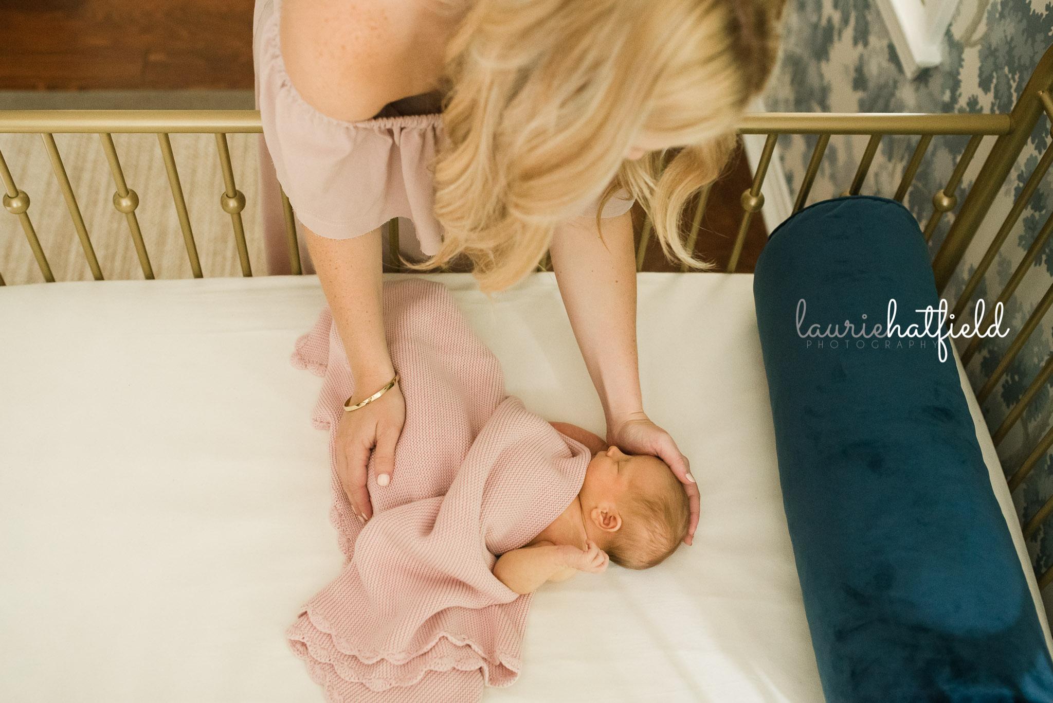 mom comforting baby in crib | Mobile AL newborn photo session
