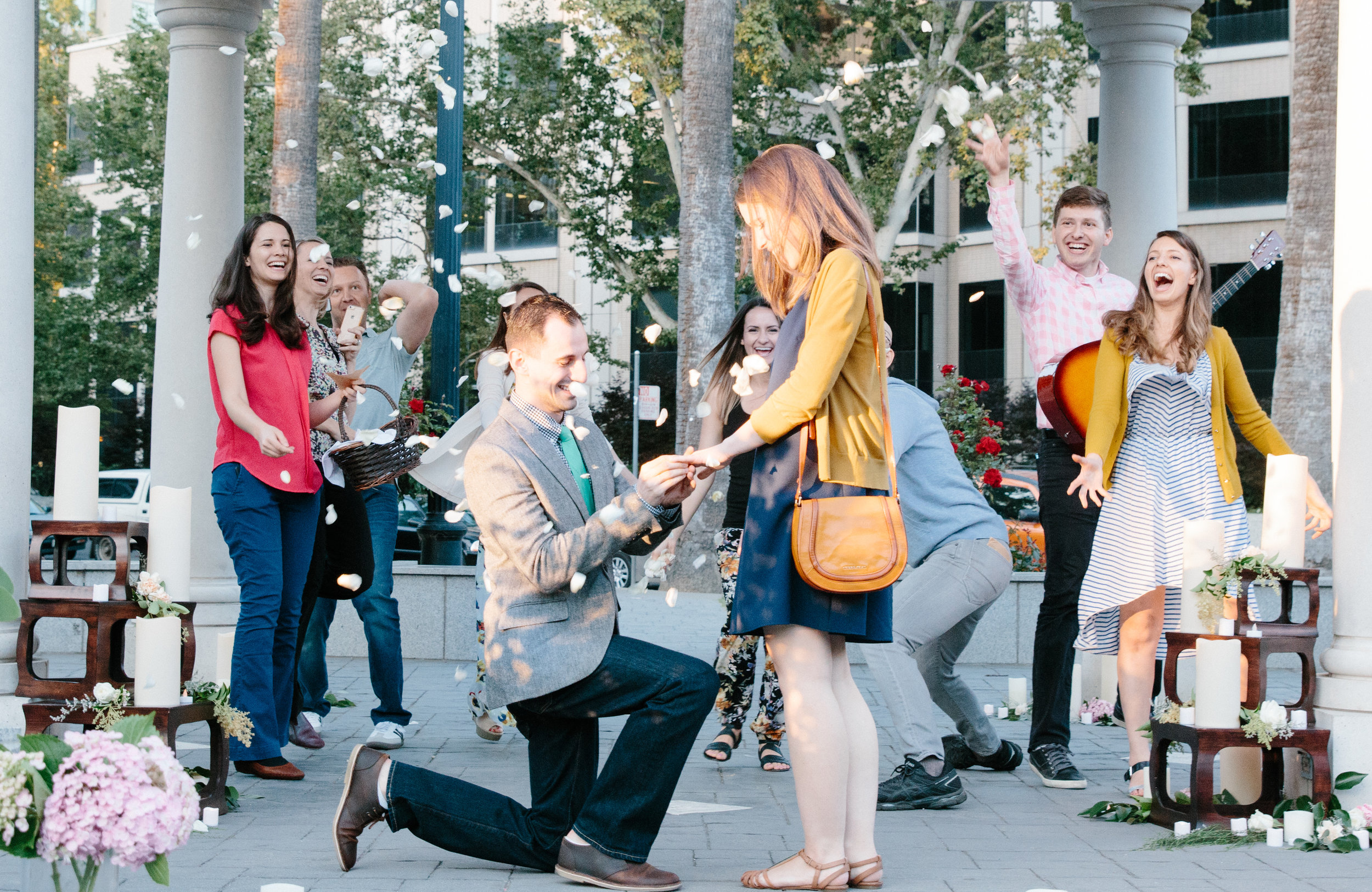 """Friends & family clapped, cheered, & tossed rose petals over the sweet couple as the future bride yelled """" YES !"""""""