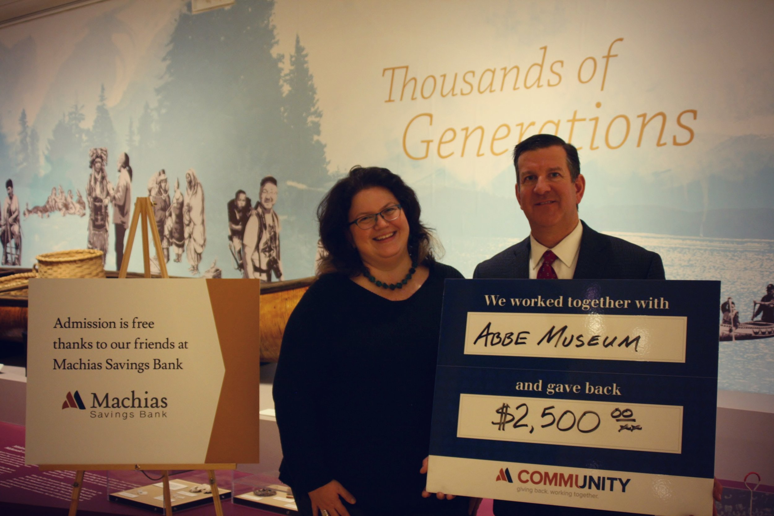 Machias Savings Bank Branch Manager Matt Horton presents Abbe Museum President and CEO Cinnamon Catlin-Legutko with a check in support of the Abbe's free admission program