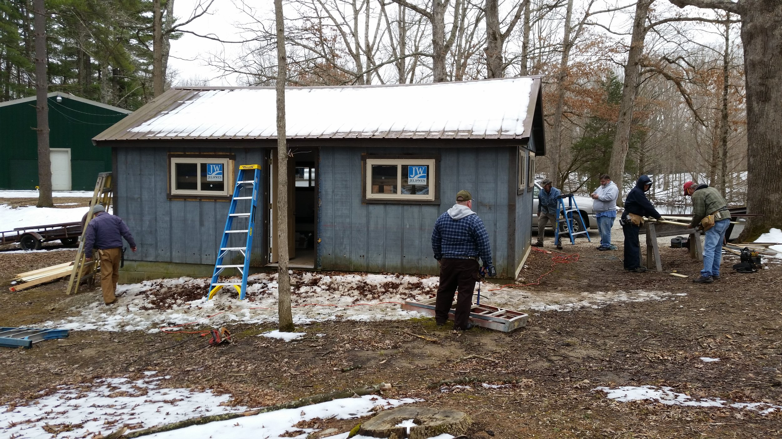 ABM of Long Run Association installing metal siding on their Cabin #17.