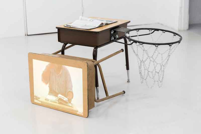 Cameron Granger;  African American Studies , 2017; Video, two school desks, the artist's 10th grade American History textbook, and Tierra's basketball hoop; 36 x 48 inches; Courtesy the artist.