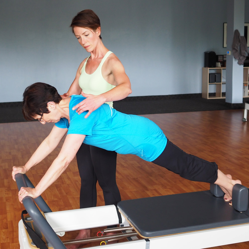 Trainer and client on Pilates reformer