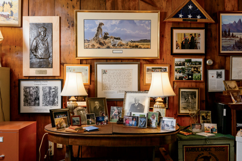 Family photos share space in Liz's den with awards and reminders of her long career. At left is a relief of Liz created by sculptor Larry Nowlan, an SCA alum. On the table, the large photo left of center shows Liz's father, Edward Sanderson Cushman, who helped instill in his daughter a love of wild places.  Mark Fleming