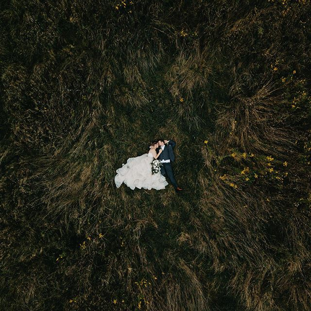 Sometimes I'll ask my clients to lay down in expensive clothes on there wedding day and they do ! Does the president have this kind of power? #ivegotthepower #drone #brideandgroom #buffaloweddingphotography #knoxfarms
