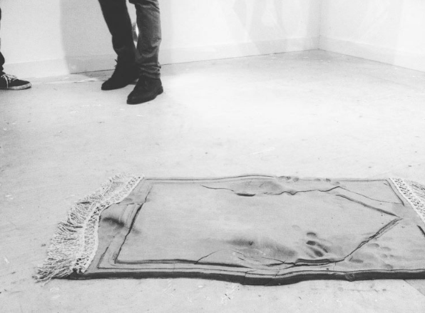 'Imprints' is a sculptural installation depicting a Muslim prayer mat. In Islamic tradition, a Muslim is obliged to perform the prayer ritual |Salah| five times a day, in which one humbles themselves in front of Allah through various actions including prostration. The sculpture is marked by the imprints left behind after a person's performance of the Salah. Made from raw clay, the material is symbolic of the Islamic belief that man and woman are created from clay. The organic and pure nature of the piece is a further allegory of the spiritually purifying conduct of worship. The artwork faces the Qiblah, the direction towards which all Muslims pray.