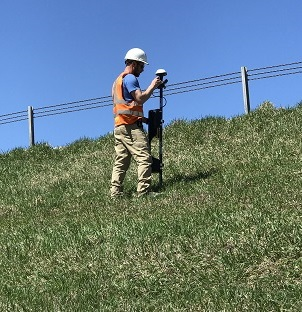 Field Technician collecting measurements of the magnetic field generated by the electric current introduced to the water leaking from the dam.