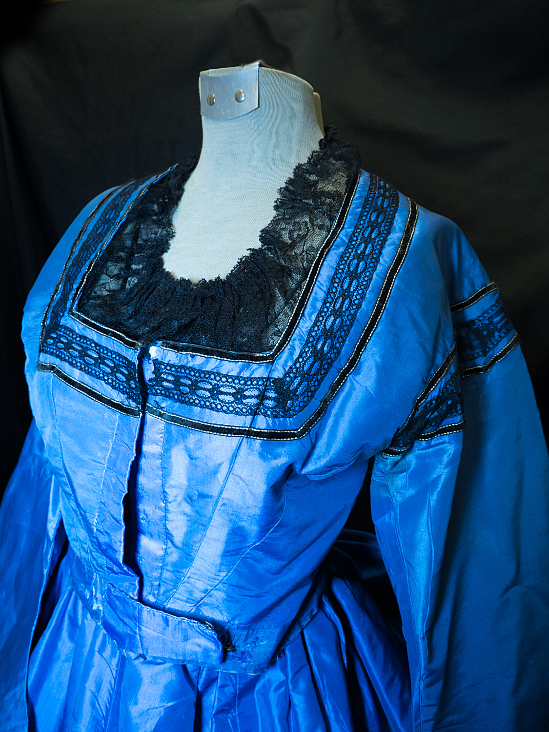Dinner dress circa 1863. Silk taffeta aniline. Blue trimmed with black laces and black velvet ribbon skirt.