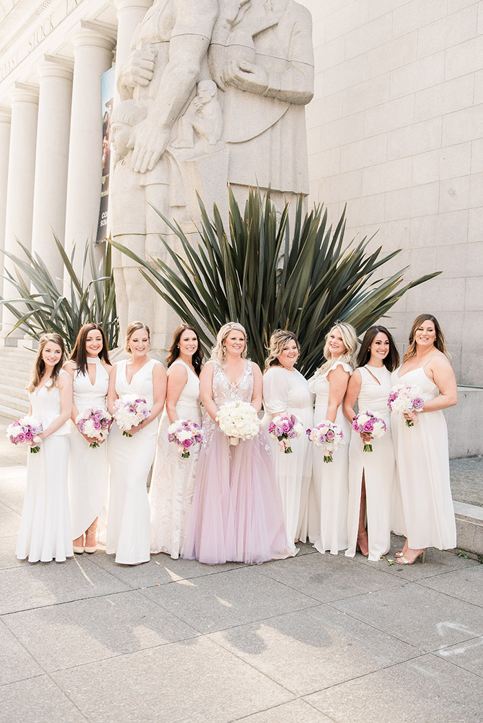 Bride Wears a Blush Wedding Dress with Bridesmaids in White