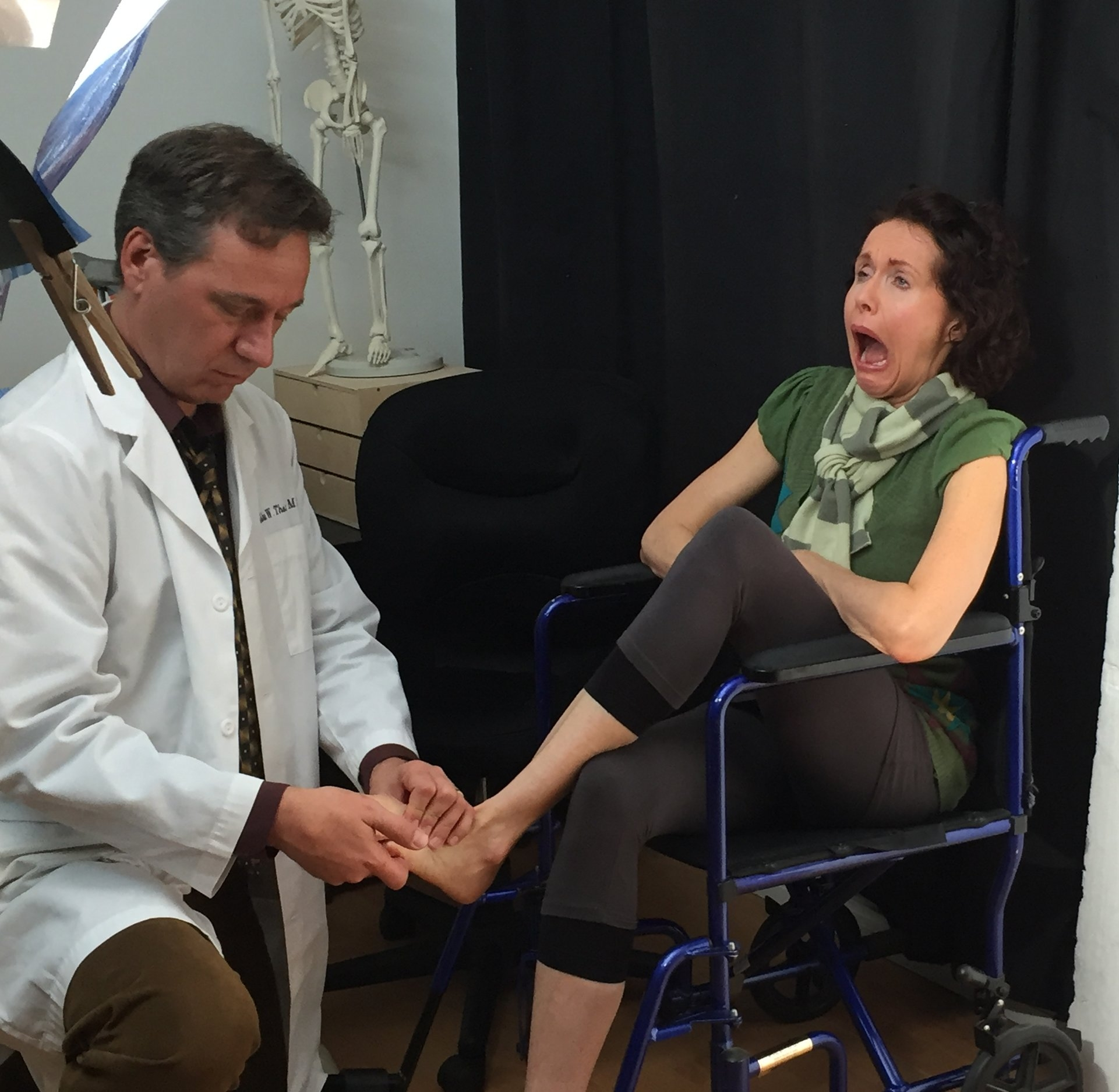 Left to Right: Demetrio James as Doctor resetting Mac's (Maura Knowles's) toes.
