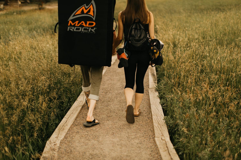 Couple walking forward on boardwalk with climbing gear