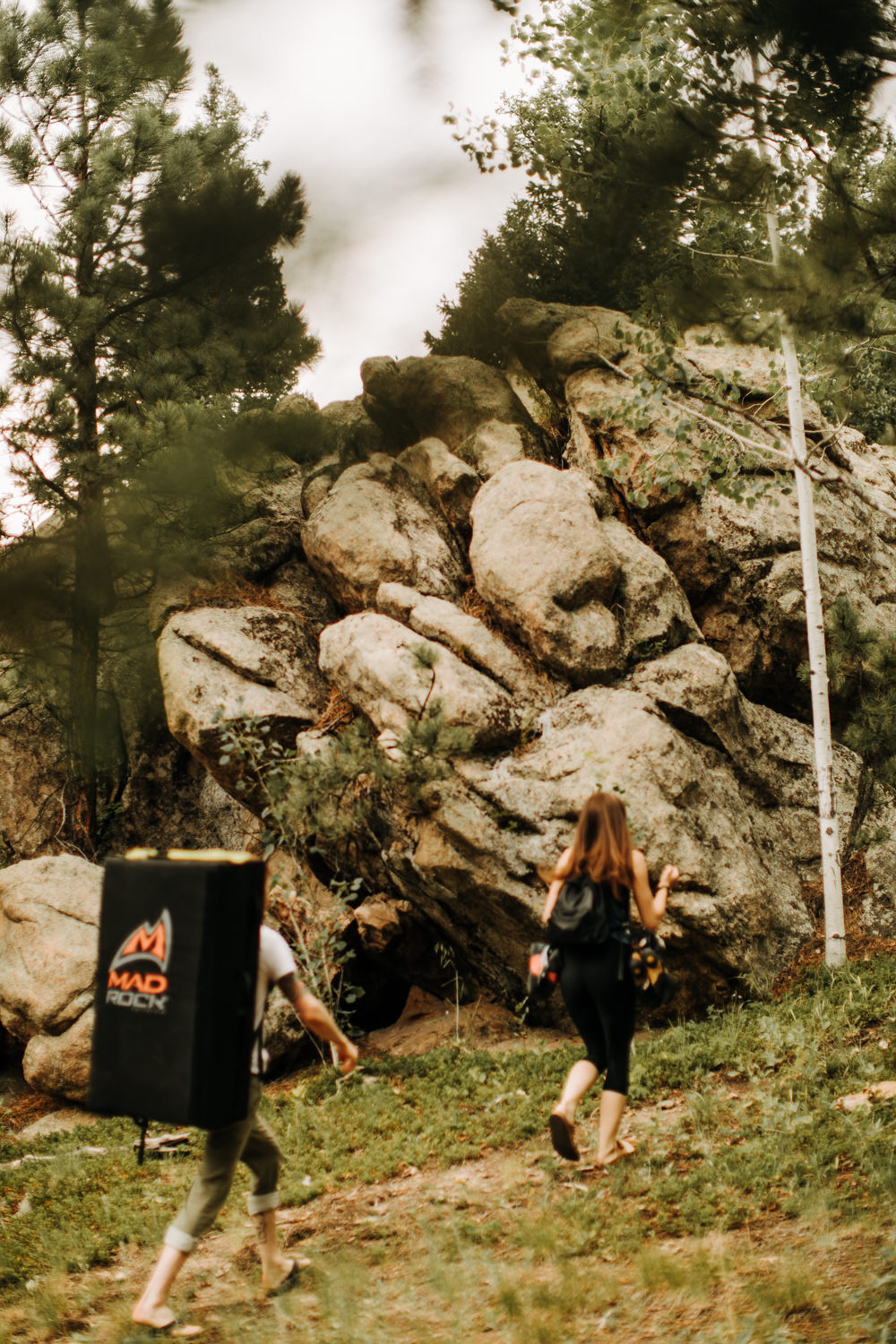 Couple walking through forested woods and boulders with climbing gear