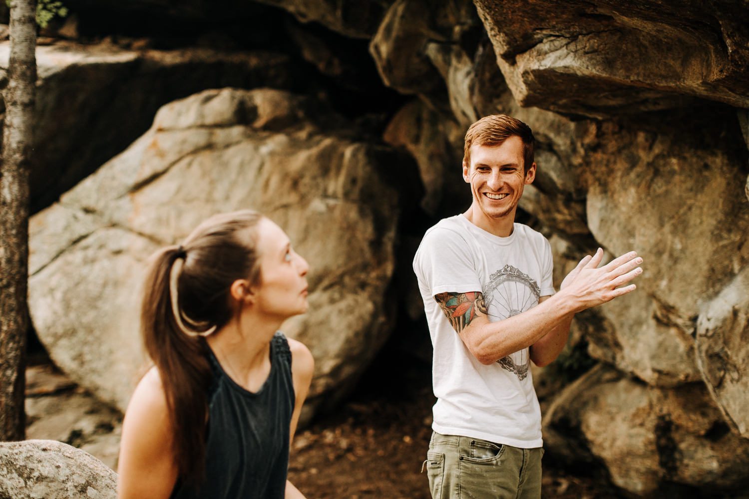 Man smiling and laughing while chalking his hands for rock climbing as a girl looks on