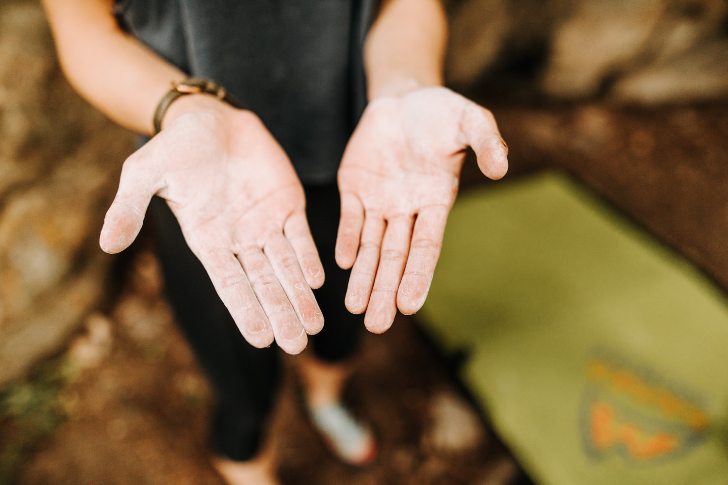 Woman showing her chalked hands for rock climbing