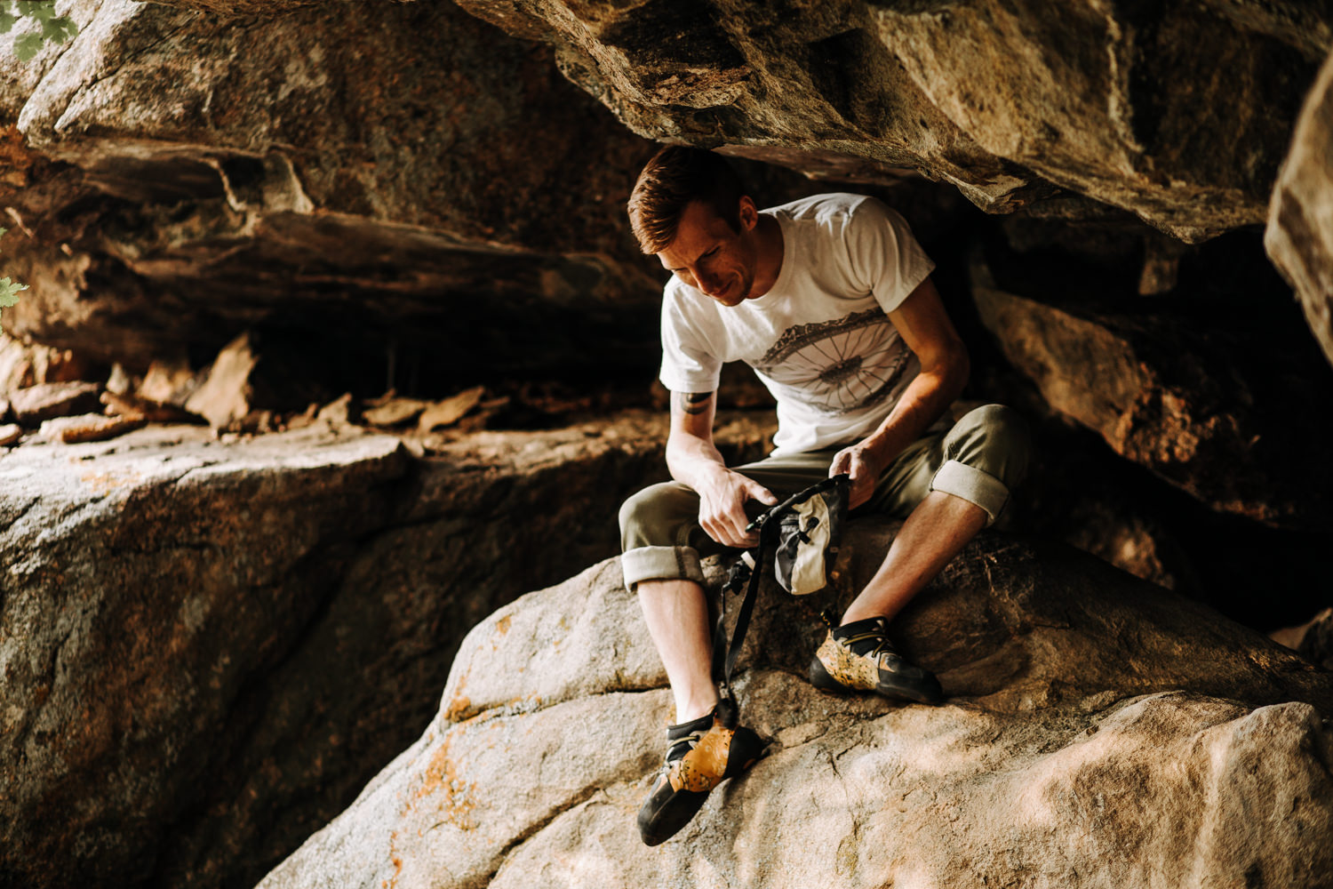 Man sitting underneath large boulder to chalk his hands while rock climbing in Evergreen