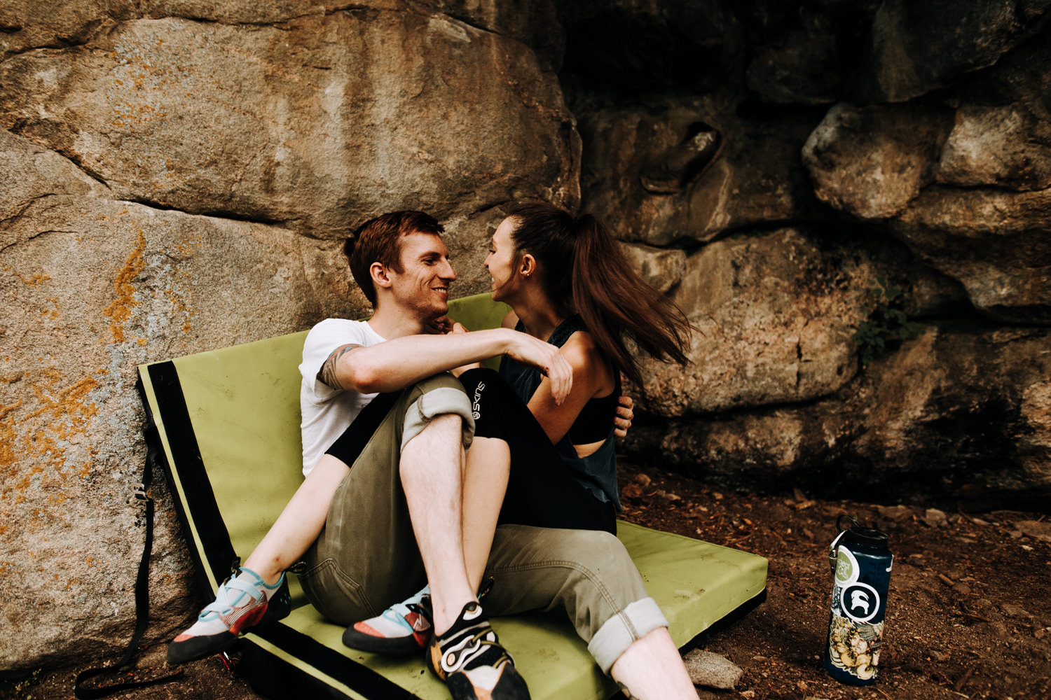 Rock climbing adventure couple sitting on bouldering pad laughing together