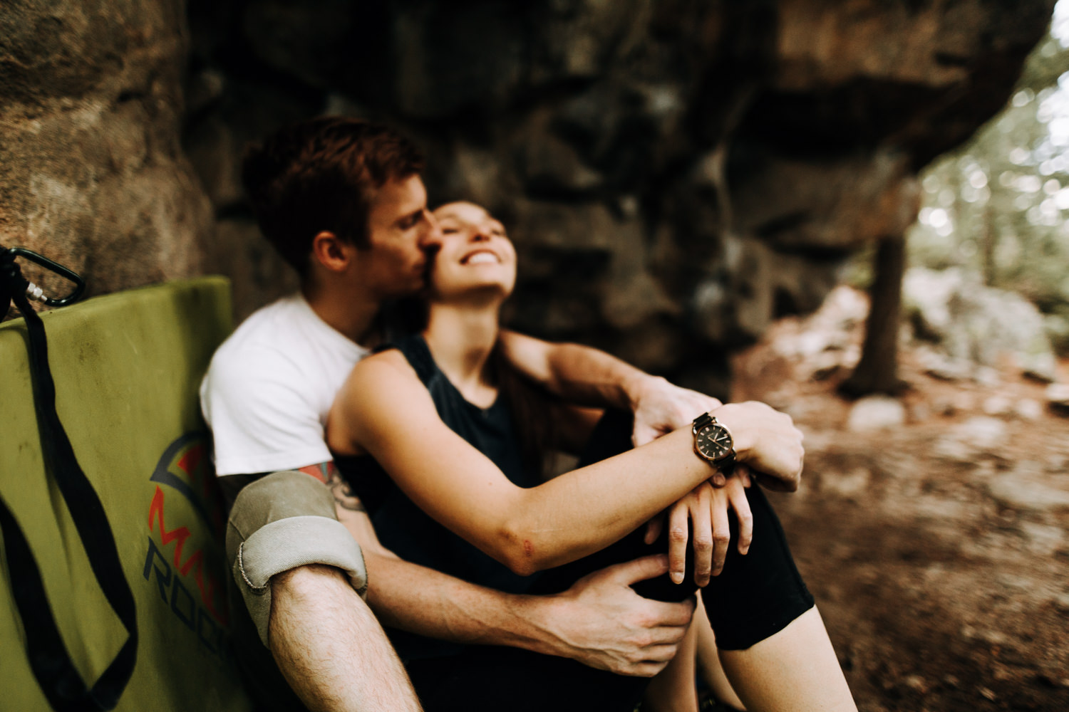 rock climbing couple adventurously kissing under bouldering problem