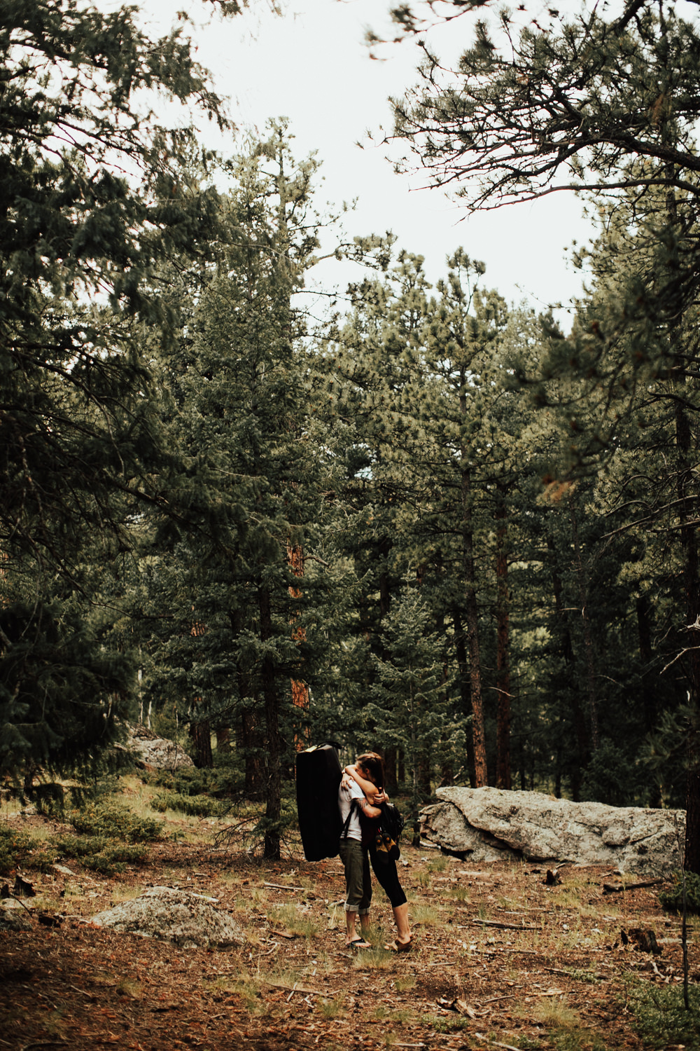 Rock climbing couple embracing in wooded area