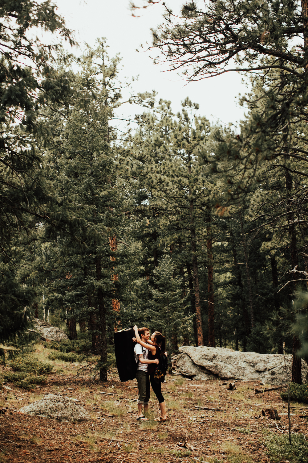 Bouldering couple kissing in the woods of Evergreen