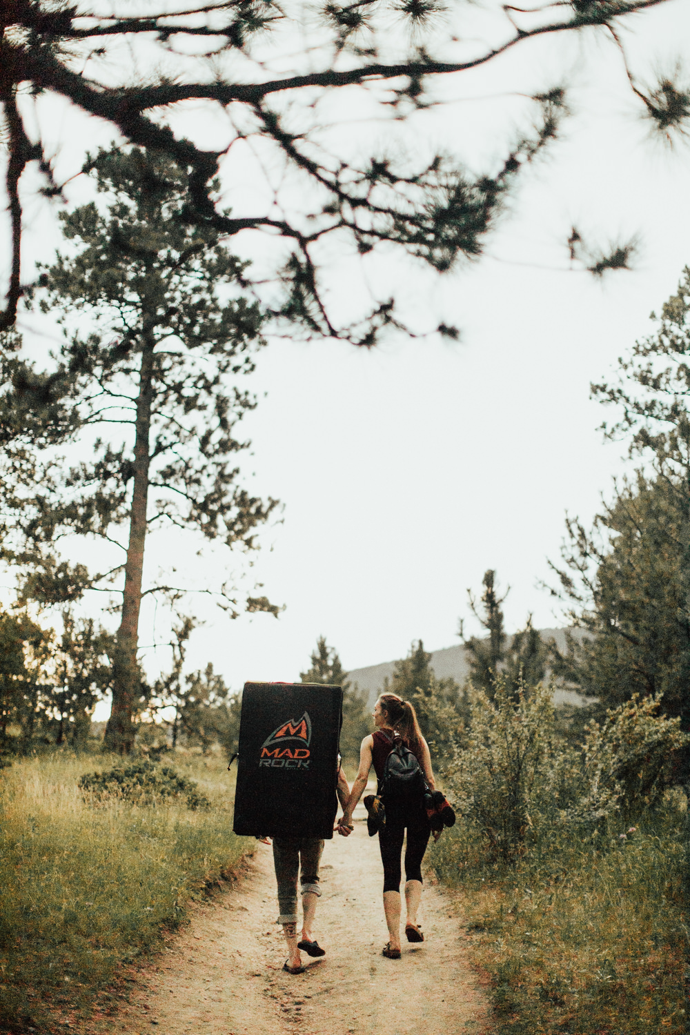 Rock climbing couple holding hands walking on a path in wooded area of Evergreen