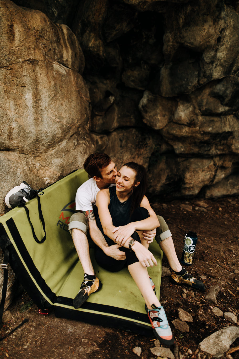 Man kissing womans cheek while sitting on bouldering pad in Evergreen