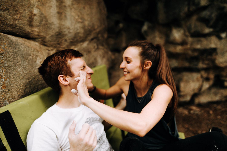 Woman putting rock climbing chalk on mans face