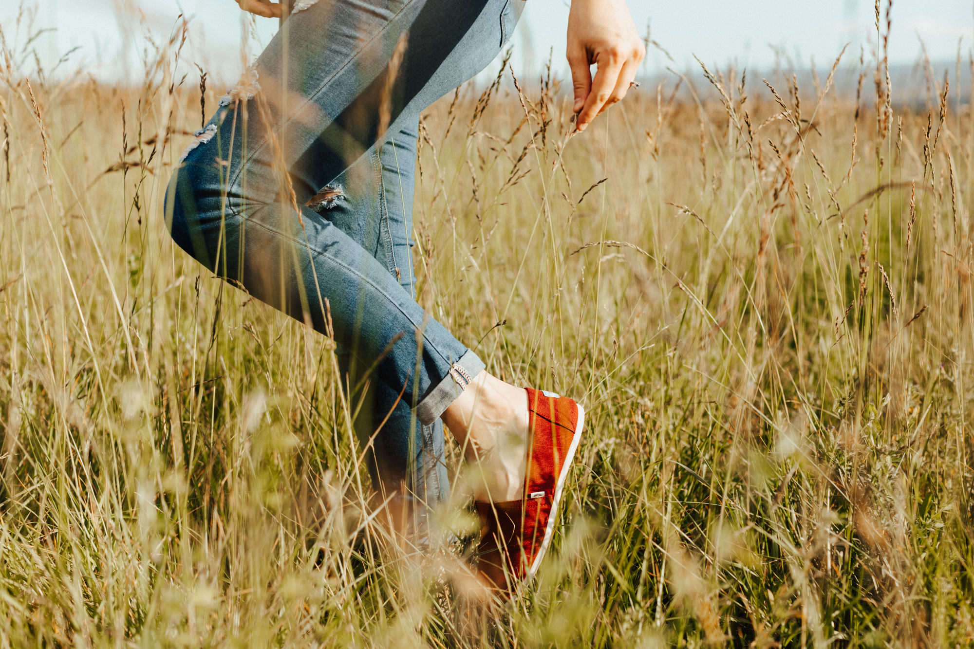 Womans legs in blue jeans with red Toms shoes in a green field