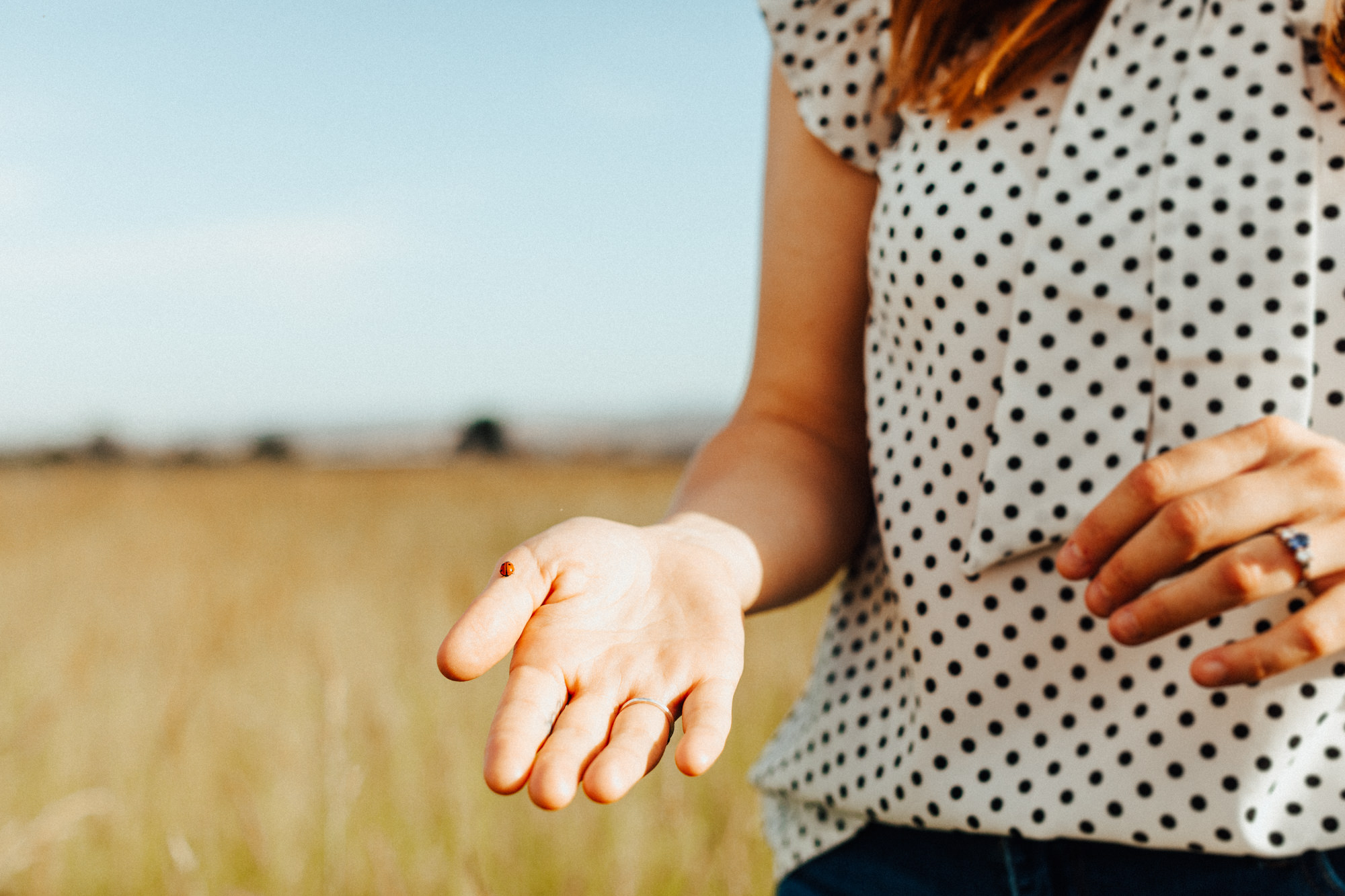 Woman holding hand out with lady bug