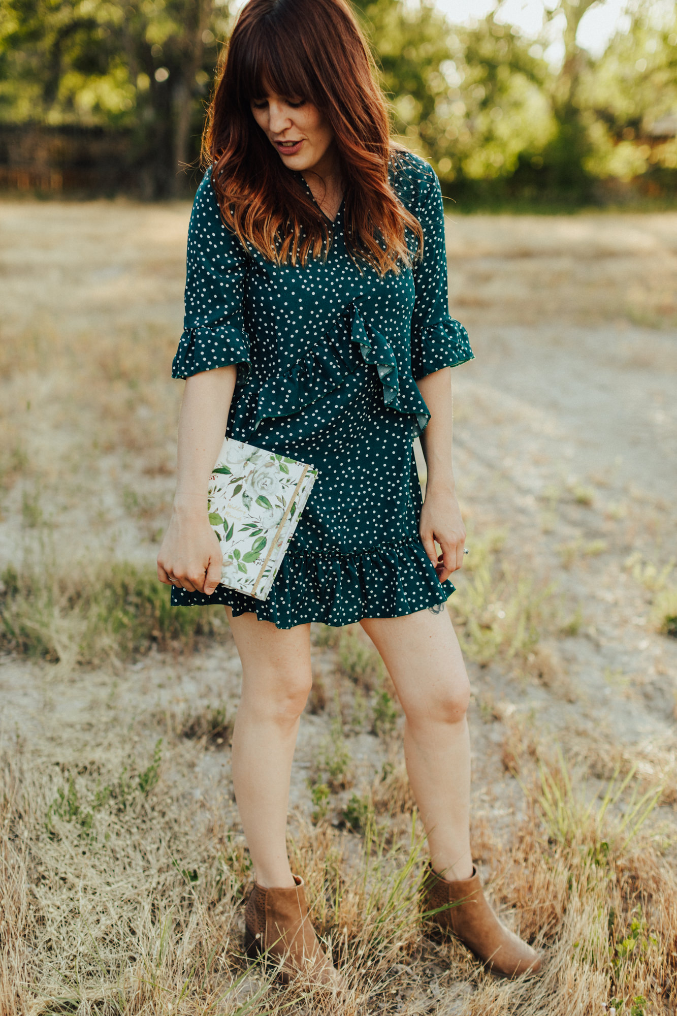 Woman in blue polka dot dress standing in a sunny field holding a wedding planner