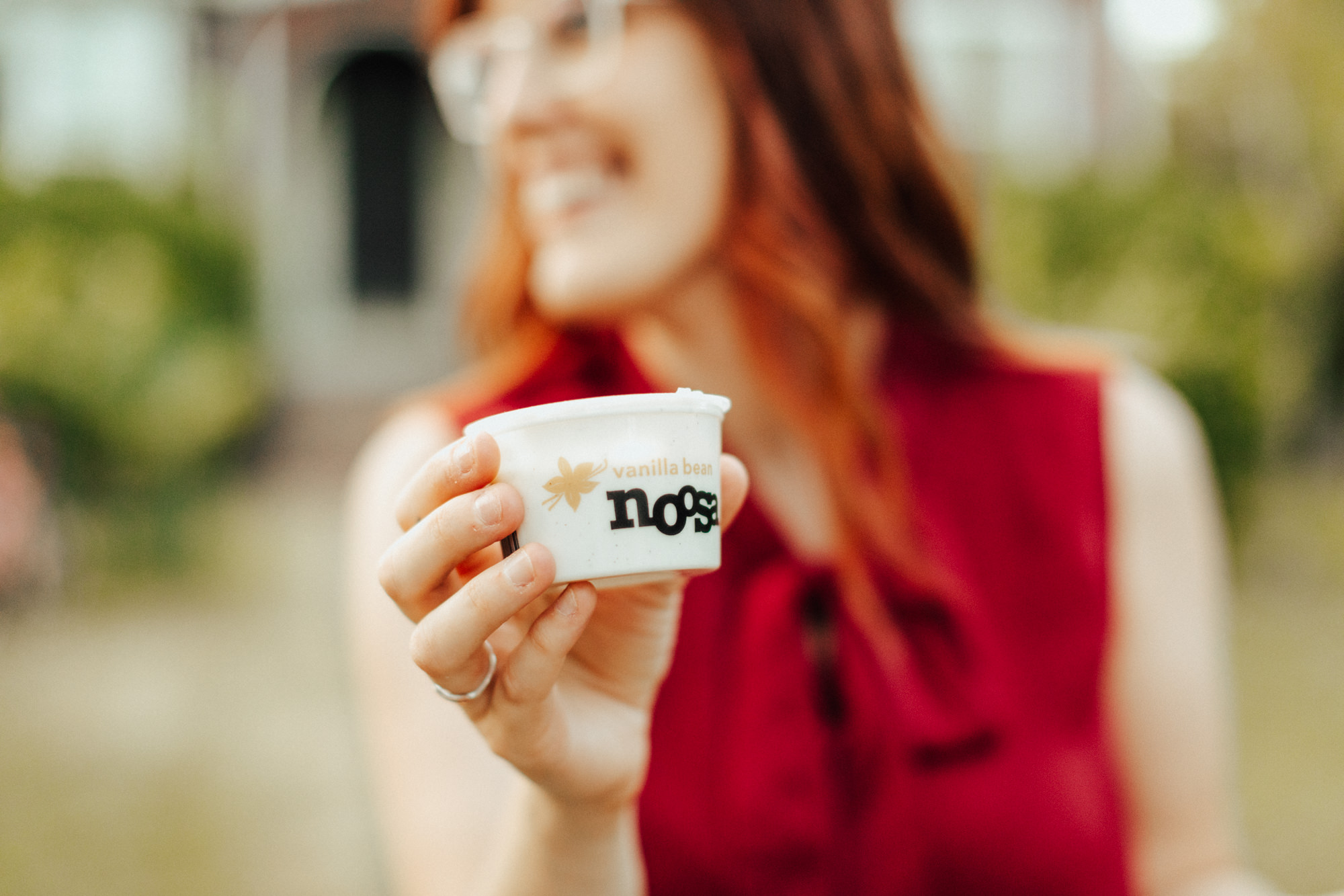 Woman smiling holding a cup of Noosa yoghurt