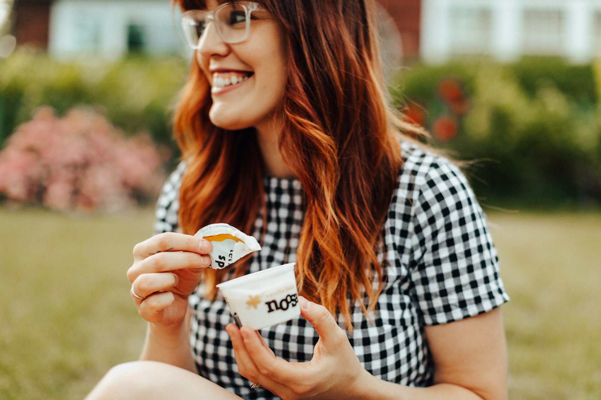 Woman smiling holding a cup of Noosa yoghurt and using the lid as a spoon