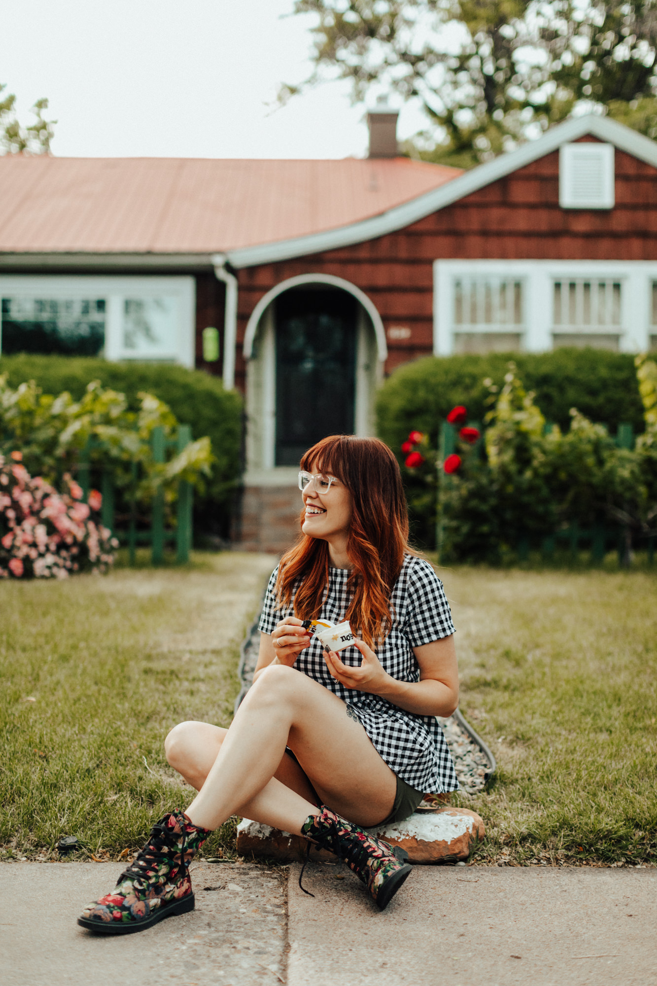 Woman sitting on the ground infront of a house eating Noosa yoghurt for brand lifestyle photography