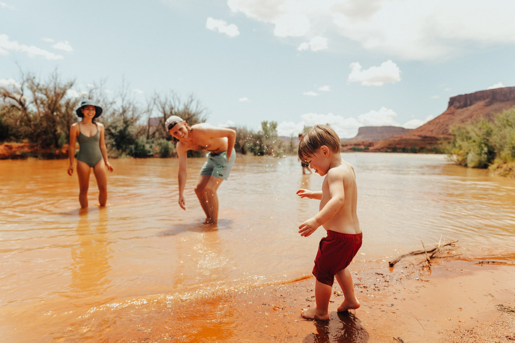 Mother and father splashing son in desert river wash