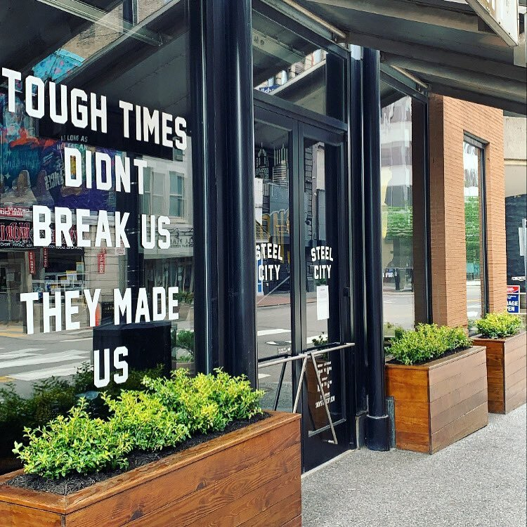 tough times didn't break us. they made us.  Steel city's storefront in downtown pittsburgh alludes to how pittsburgh has helped to lead the nation through tough times using innovation.