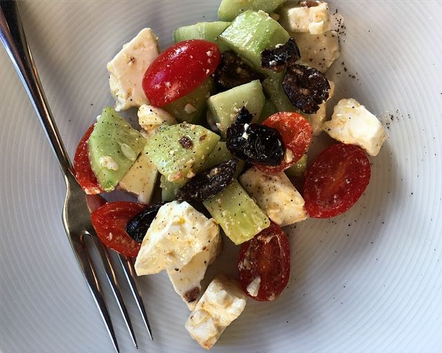 Feta Salad                                                  Photo ©Evie Saffron Strands   The heat of July brings with it a longing for cooling salads – the last thing we want to do at this time is stand at a hot stove.    This 'recipe' fits the bill. I've deliberately called it Feta Salad, rather than Greek Salad, as this assemblage is the way we make it and may not bear scrutiny as truly authentic. You could add thinly sliced red onion, which our Greek customers would approve of, I think, and some add sliced green pepper too. Whether you peel your cucumber or not is a matter of preference and, maybe, the variety of cucumber.     Feta Salad    (Serves 4)   300-400g Feta Cheese, roughly crumbled  2-3 small Cucumbers (or 1 large), cut into chunks  2 vines of Tomatoes, halved  150g Black Olives (preferably Kalamata)  1 smalll Red Onion, thinly sliced (if liked)  1 green pepper (if liked)  1 tablespoon Red wine vinegar or Lemon juice  4 tablespoons Extra Virgin Olive Oil  A little Fresh or dried Oregano (unless using herbed olives)  Mix together the wine vinegar/lemon juice and olive oil and add the oregano. Add the rest of the ingredients and mix carefully but thoroughly.  Particularly good served with Pita Bread to mop up the juices.